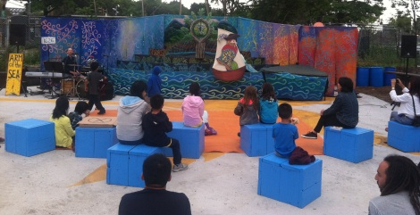 """Local families enjoy performance by Arm-of-the-Sea Theater's """"City that Drinks the Mountain Sky"""" on Pier 42 in July 2013."""